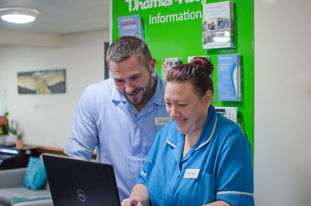Thames Hospice 2 people looking at laptop